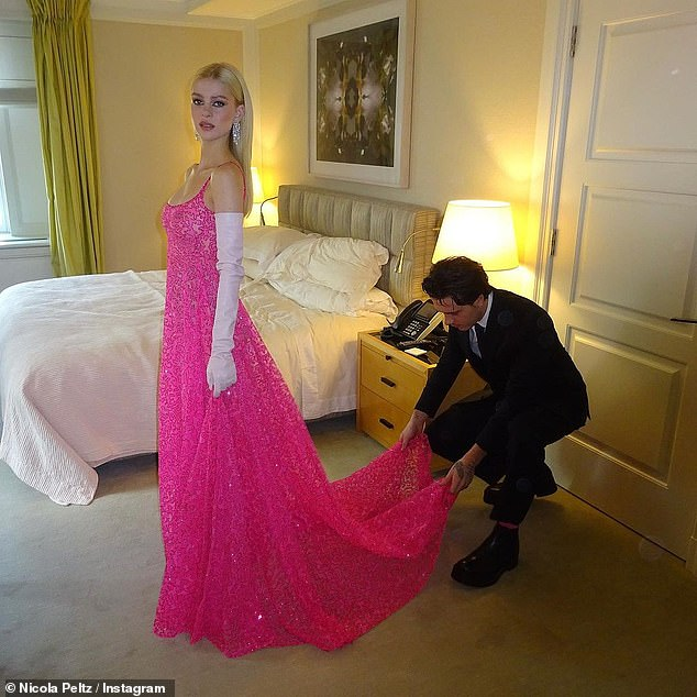 Doting: Meanwhile Brooklyn, 22, looked dapper in a black suit as he was seen adjusting her outfit in their hotel room