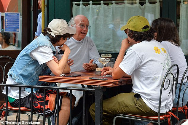 Storyteller: The 74-year-old godfather of cringe comedy was also joined at the table by his daughter Romy (R) and a man (2-R) resembling her boyfriend Josiah Adams