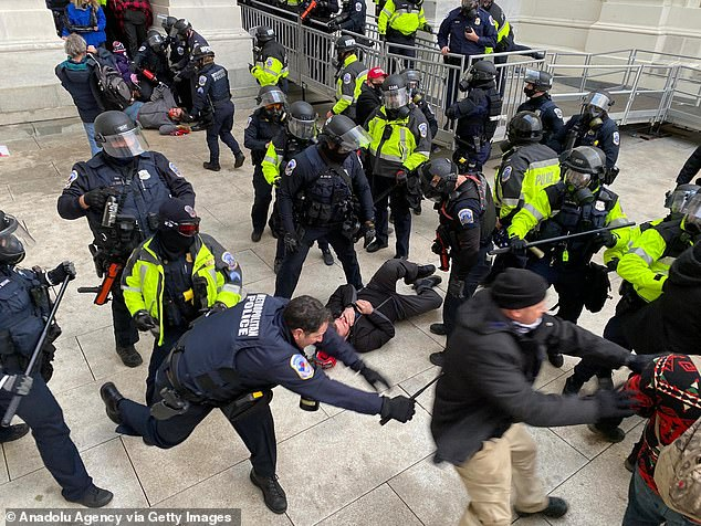 Officers are seen securing the entrance to the U.S. Capitol against the rioters