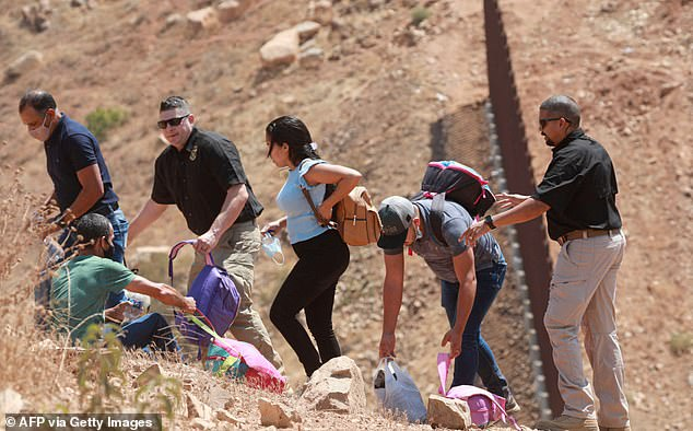 Customs and Border Patrol agents apprehend a group of Brazilian migrants who illegaly crossed the border in Otay Mesa, California on August 13. Fox News reported Wednesday that more than 200,000 migrants were apprehended last month