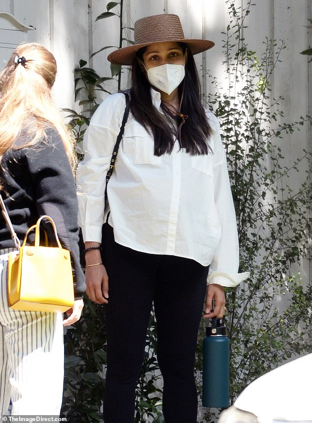 Covered up: Freida Pinto was seen fully covered in a long-sleeve button down white shirt, black leggings, and black Nike sneakers as she waited for a ride in Los Angeles on Wednesday