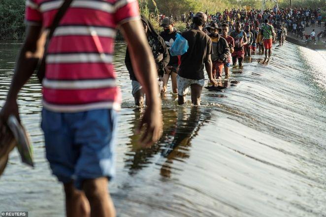 Migrants seeking asylum in the U.S. walk in the Rio Grande river near the International Bridge between Mexico and the U.S.