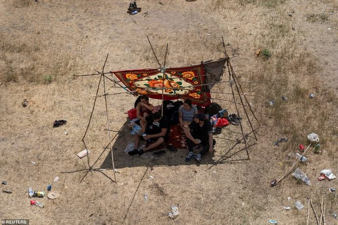 Migrants seek shade in a makeshift tent near the International Bridge between Mexico and the U.S. on Thursday