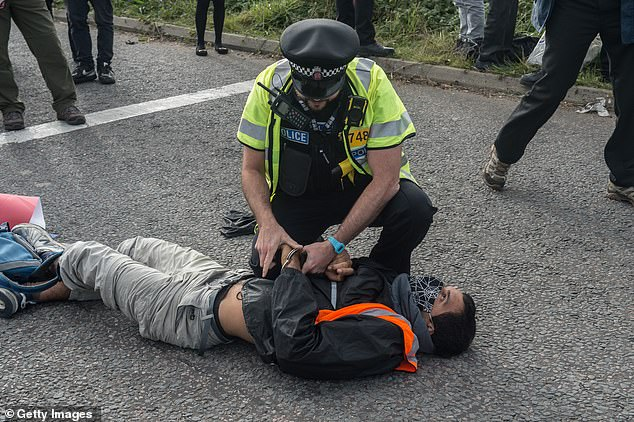 Police arrest activists as protesters from the Insulate Britain pressure group block a roundabout on the M11 this morning
