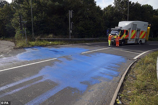 Highways England workers on the exit slip road of the M25 motorway near Leatherhead after protestors blocked the road and left paint on it