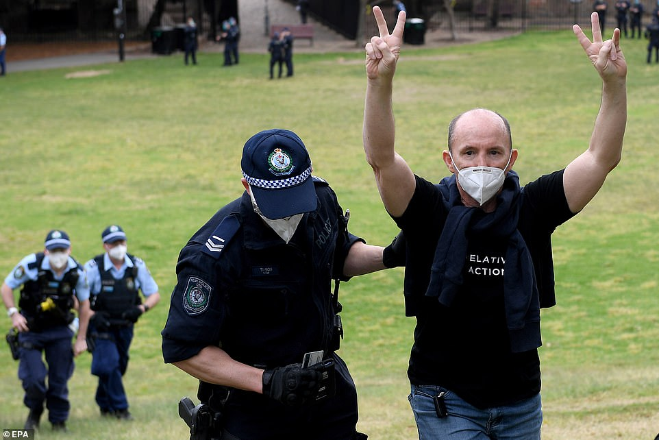 Police made a series of arrests at Sydney Park in St Peters in the inner-west (pictured, an officer takes a man for questioning)