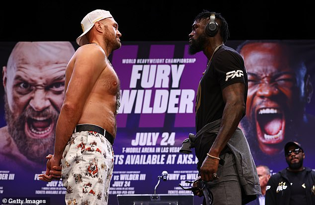 Tyson Fury's father, John, predicts that his son will force Deontay Wilder (R) into retirement
