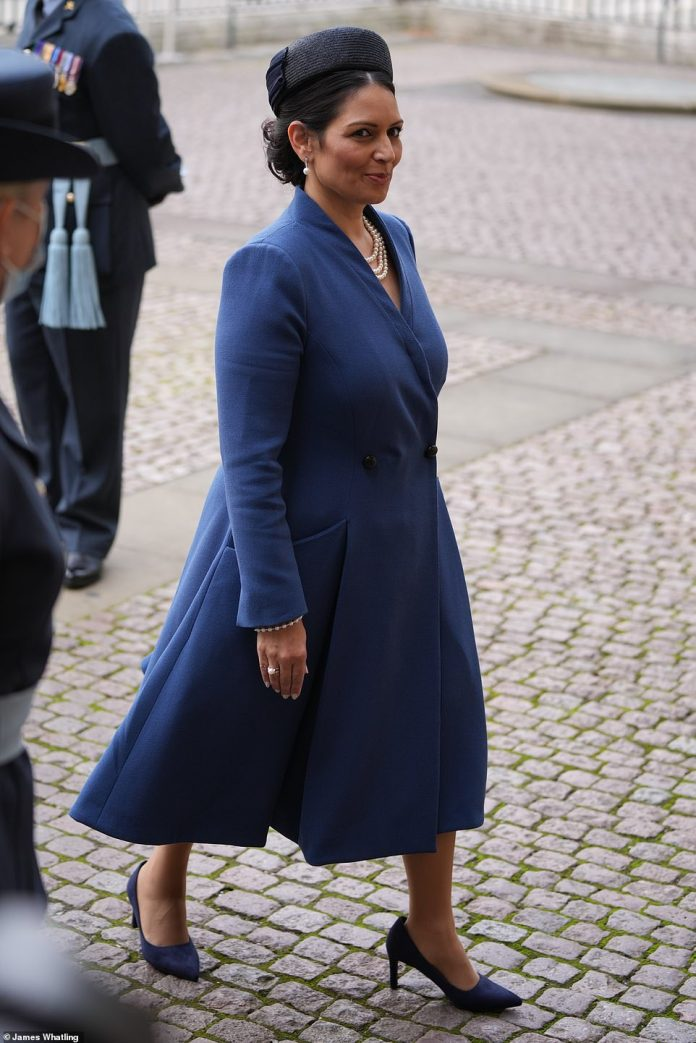 Home Secretary Priti Patel, who wore a mid-length navy dress jacket and charcoal pillbox hat in Royal Air Force blue