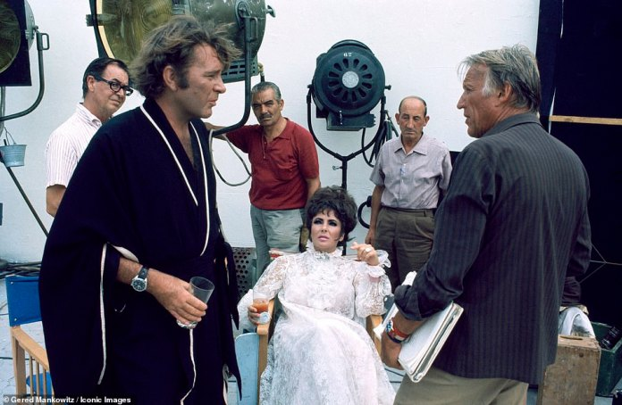 Taylor's then-husband, wearing a dressing gown, is pictured talking to director Joseph Losey on set