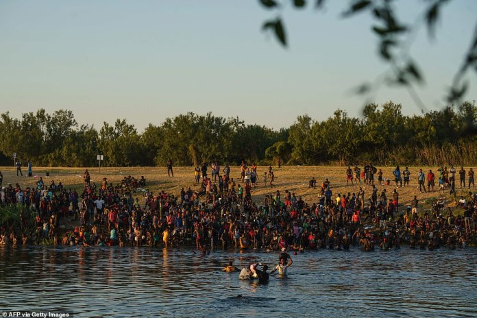 Migrants are pictured on the banks of the Rio Grande River on Sunday as DHS ramps up removal flight efforts and attempts to block asylum-seekers from getting to the U.S. through the Mexico border near Del Rio