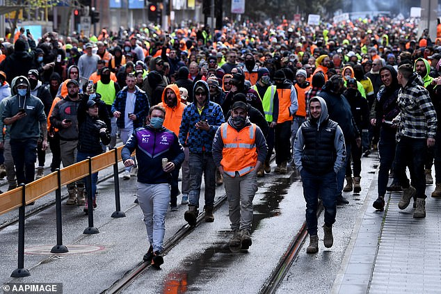 Hundreds of protestors - many wearing hi-vis - marched towards state parliament to rally against mandatory vaccine orders