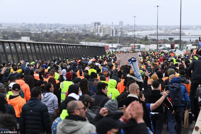 Thousands of construction workers are pictured protesting on the West Gate Bridge on Tuesday afternoon as the demonstration moved out of Melbourne's central business district