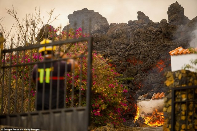 A fireman watches helplessly as tons of molten rock consume a house on La Palma, one of 166 destroyed so-far