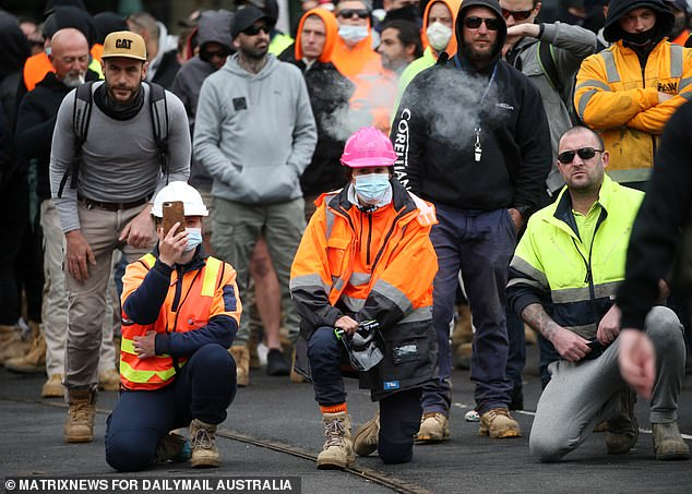 Anti-vax protesters in Melbourne are seen blocking off the street by kneeling on the road