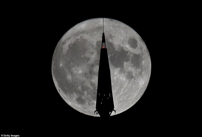 The Full Harvest Moon rises behind the top of the antenna at One World Trade Center in New York City.  This is the fourth full moon of the summer this year, and will peak before the equinox actually occurs, making it the summer moon