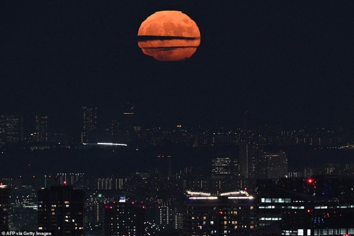 The full moon is seen from Tokyo's Roppongi district.  It is the full moon closest to the autumnal equinox – the moment the Sun is seen crossing the celestial equator – on September 22