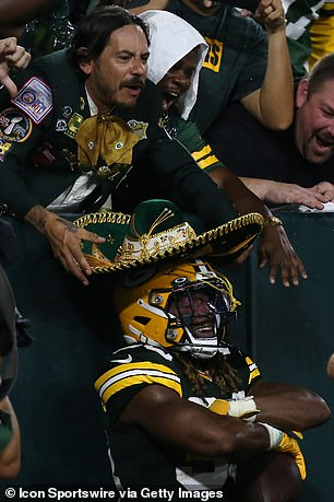 A fan puts his sombrero on Green Bay Packers running back Aaron Jones (33) during a game between the Green Bay Packers and the Detroit Lions at Lambeau Field on September 20, 2021 in Green Bay,