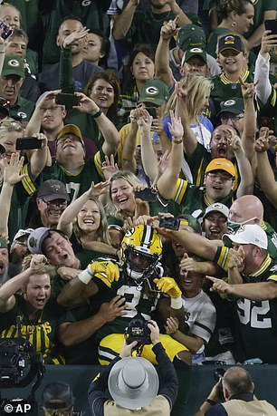 Green Bay Packers' Aaron Jones celebrates with fans after catchiong a touchdown pass during the first half of an NFL football game against the Detroit Lions Monday