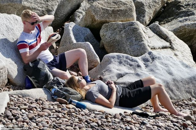 Sunseekrs make the most of the lovely sunny weather on the beach in Sidmouth, Devon