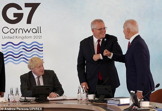 British Prime Minister Boris Johnson looks on as Australian Prime Minister Scott Morrison and U.S. President Joe Biden bump elbows during the G7 conference in Cornwall in June