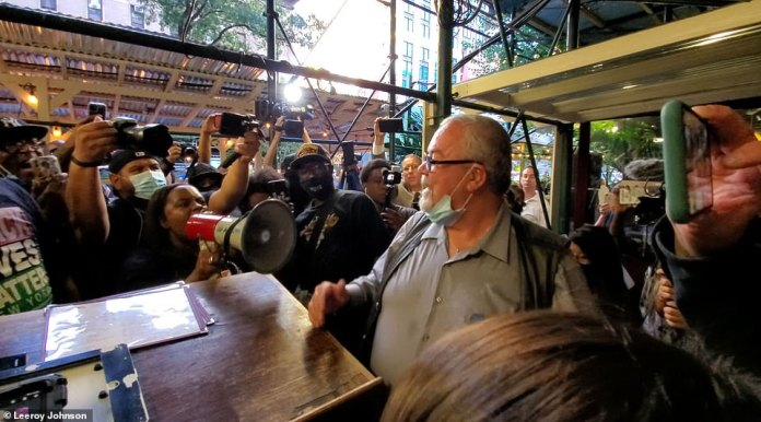 Black Lives Matter protesters gather outside Carmine's, an Italian restaurant on Manhattan's Upper West Side, on Monday