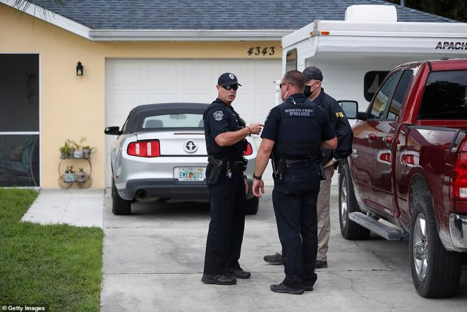 An FBI agent talks with a North Port officer while they collect evidence from the Laundries' family home