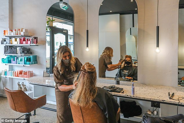 Hairdressers have urged the state's health officials to scrap the limit while labelling the rules as 'unfair' in comparison to gyms (pictured, resident has her hair blowdried)