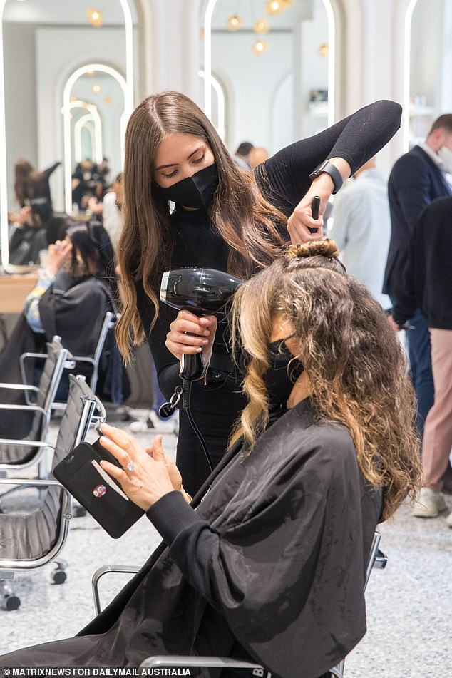 Hairdressers are to reopen to fully vaccinated clients once the state's 70 per cent vaccination target is achieved (pictured, a woman has hair styled during eased Covid restrictions)