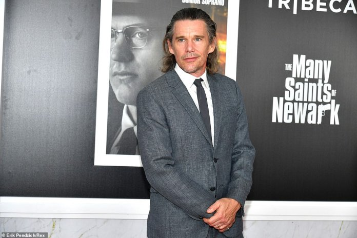 Riding solo:Ethan Hawke rode solo as he arrived in a charcoal grey suit and matching tie to The Many Saints Of Newark premiere
