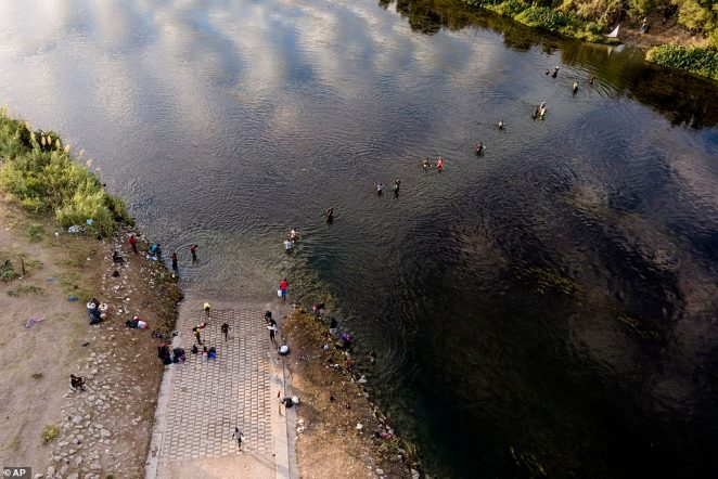 Migrants, many of them from Haiti, are pictured wading back and forth between Texas and Mexico on Wednesday. At the weekend an estimated 14,000 migrants were sheltering in Del Rio