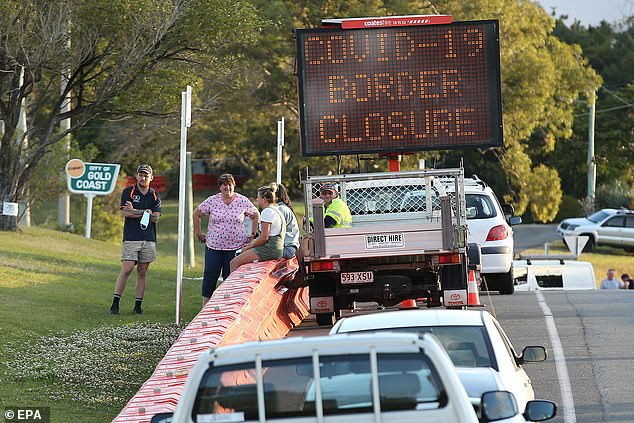 PremierPalaszczuk will keep borders closed between NSW and Victoria, meaning many families will go another Christmas without seeing their loved ones (pictured, people talk over barriers at the Tweeds Head border between Queensland and NSW)
