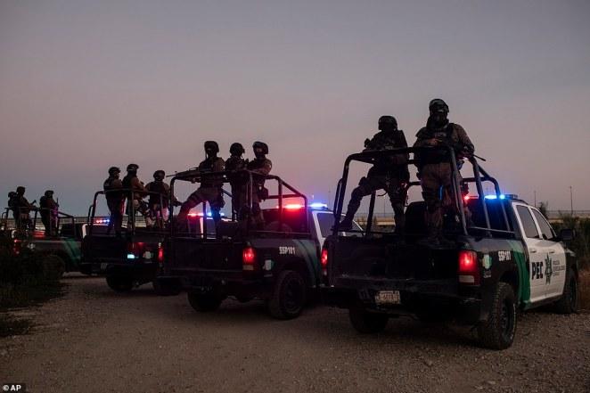 Mexican police stand guard near the Rio Grande river in Ciudad Acuna, Mexico, at dawn Thursday on the border with Del Rio