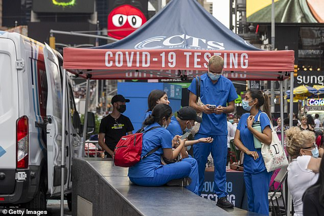 Healthcare workers wearing masks stand in front of a COVID-19 testing booth in Times Square on August 31, 2021 in New York City.