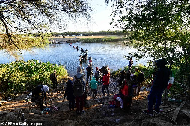 Here migrants cross the Rio Grande river on Thursday back to the U.S. from Ciudad Acuna, Mexico to a makeshift camp where they await processing as they seat asylum