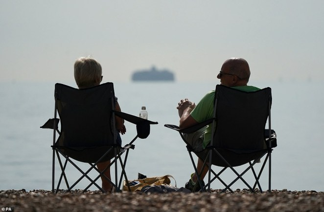 Blustery showers and plunging temperatures are on the way from Monday, bringing an end to the September sunshine many of us have enjoyed. Pictured: A couple sit on fold-out picnic chairs on Southsea beach in Hampshire