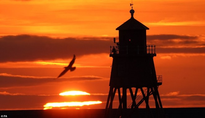 The warm spell has gone some way to console sun-starved Britons who spent much of the summer waiting for the sun to break through the clouds to no avail. Pictured:Sunrise at the Herd Groyne lighthouse in South Shields on Wednesday