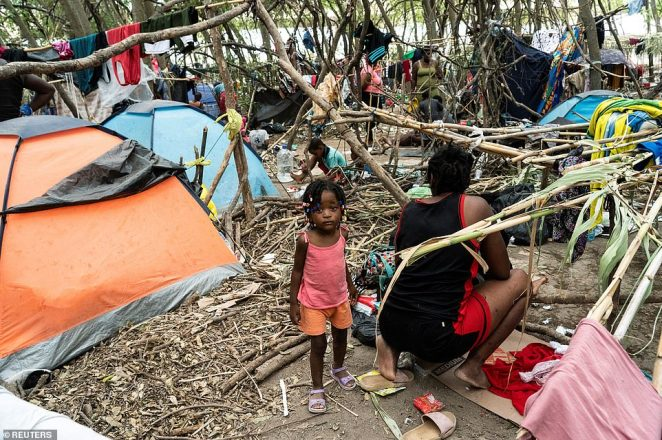 A young girl stands in the place that she currently calls home in a makeshift camp under the Del Rio bridge in Texas