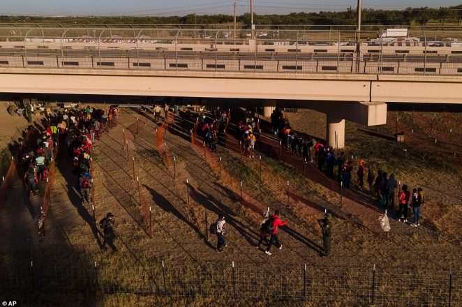 Migrants from Haiti wait in line on Thursday to board buses near the Del Rio International Bridge