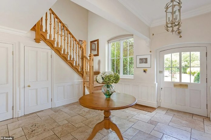 The entrance has tiled floors, light-colored walls and an oak staircase that leads to the first-floor bedroom