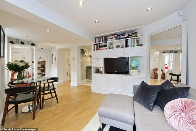 The walls are painted a clean white and are complimented by pale wood floors and large bay windows, flooding the interiors with light