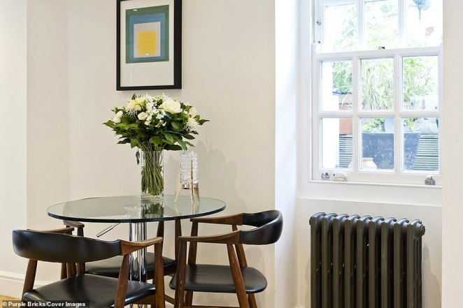White-painted walls help make the interior feel more spacious (Pictured: Small glass dining table with two chic black leather chairs)