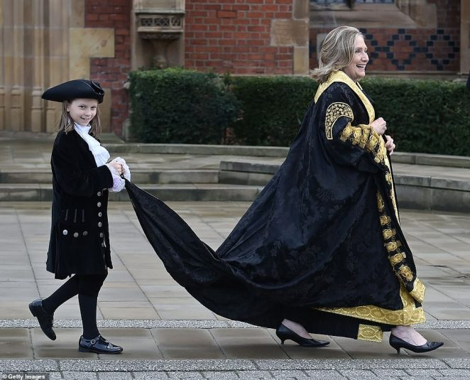 The former US secretary of state, who is the first woman appointed as chancellor of the Belfast academic institution, attended an installation ceremony in the Northern Irish city on Friday morning. Above: Clinton smiles as her gown is held up to stop it being dragged along the ground
