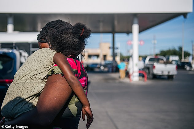 A migrant mother carries her child while after being released at the Stripes gas station in Del Rio this week. The gas station is used as a Greyhound bus stop