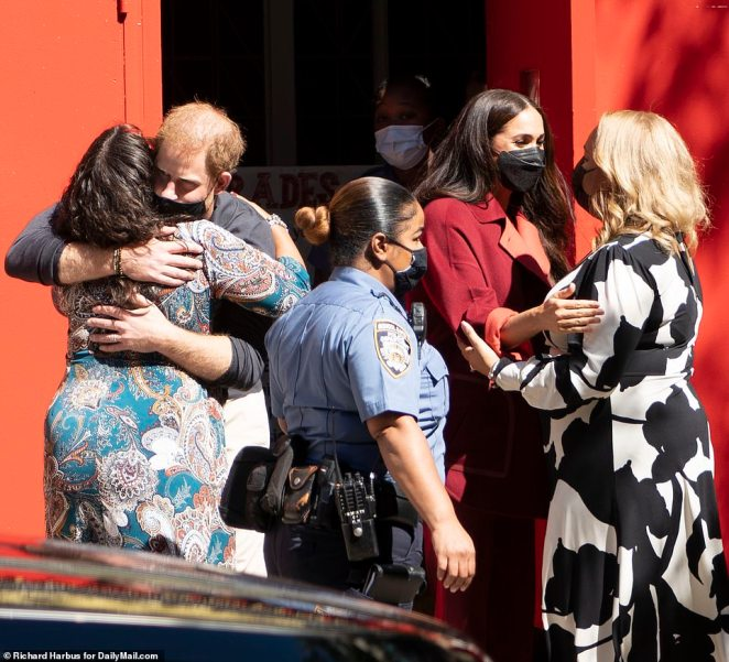 Meghan and Harry hug people at the school goodbye as they leave to embark on the remainder of their day's meetings