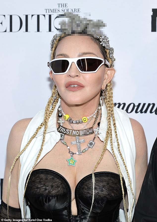 Madonna, 63, shuffles around at the premiere of her new concert film flashing a bustier, miniskirt and fishnets, a diamante tiara declaring 'F*** You' and a necklace urging fans to 'Trust No B****'