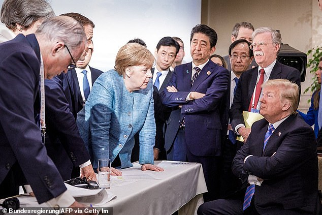 US President Donald Trump (R) talking with German Chancellor Angela Merkel (C) and surrounded by other G7 leaders during a meeting of the G7 Summit in La Malbaie, Quebec, Canada, in June, 2018