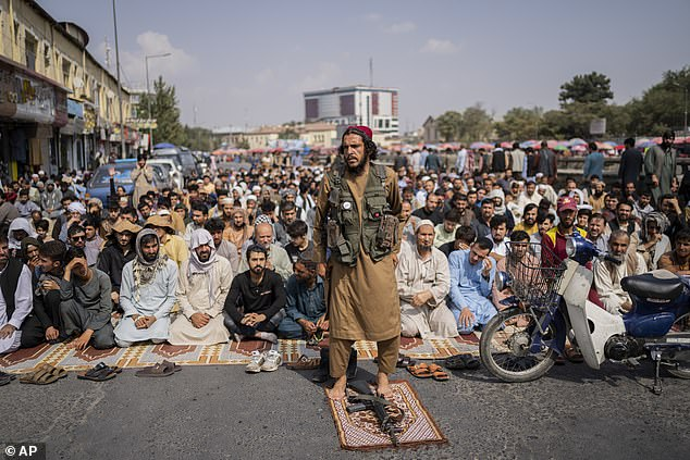 A Taliban fighter, foreground, and a group of Afghan men attend Friday prayers in Kabul, Afghanistan, on Friday
