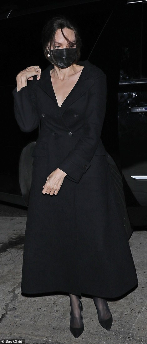 Chic: The estranged second wife of Brad Pitt wore a black double-breasted trench coat, matching pumps, and an Yves Saint Laurent purse
