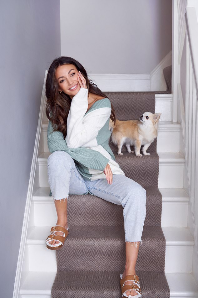 All smiles: She posed on the stairs in her comfy sweater as her dog eyed her questioningly