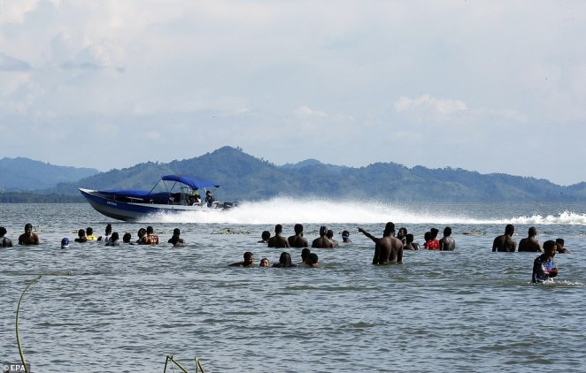 Migrants are seen in the water off of a beach in Necocli as a motor boat passes by